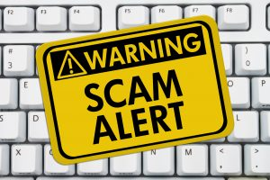 Attorney Email Scams & Data Breaches Computer keyboard keys with warning sign with words Scam Alert, Scam Alert